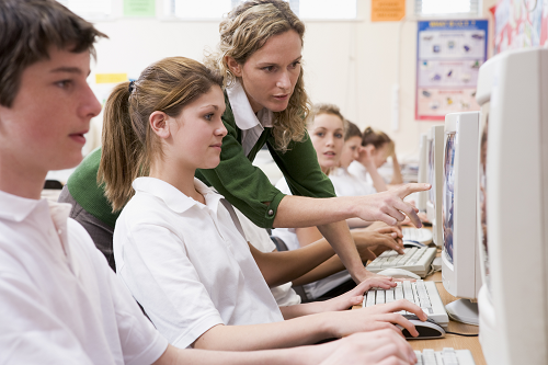 Teacher in green sweater helping female student at computer.
